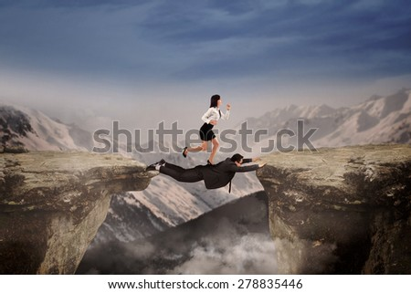 Businesswoman trust on her friend to help she through the cliff as the business obstacle - stock photo