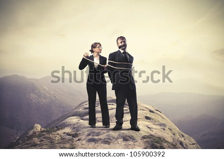 Businesswoman tying tight a businessman on a mountain peak - stock photo