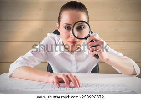 Businesswoman typing and looking through magnifying glass against bleached wooden planks background - stock photo