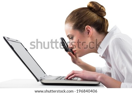 Businesswoman typing and looking through magnifying glass on white background