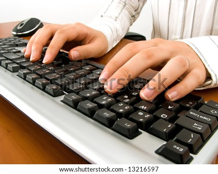 Businesswoman typing in the computer keyboard and using a mouse - stock photo