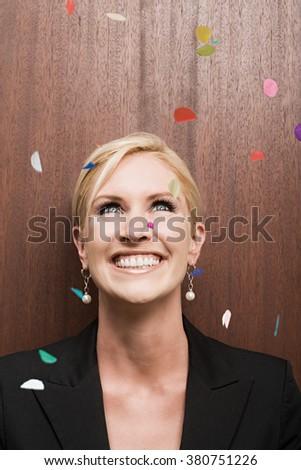 Businesswoman under falling confetti - stock photo