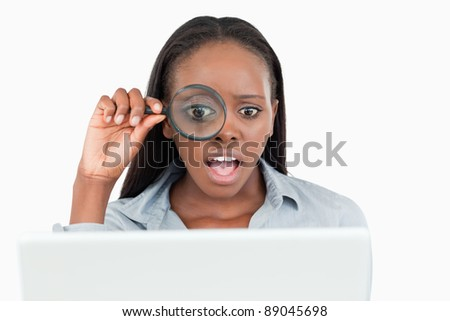 Businesswoman using a magnifying glass to look at her notebook against a white background - stock photo