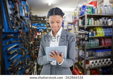 Businesswoman using a tablet with colleagues behind against full store room - stock photo