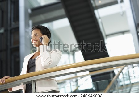 Businesswoman Using Cell Phone on Balcony - stock photo
