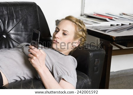 Businesswoman Using Cell Phone on Sofa - stock photo