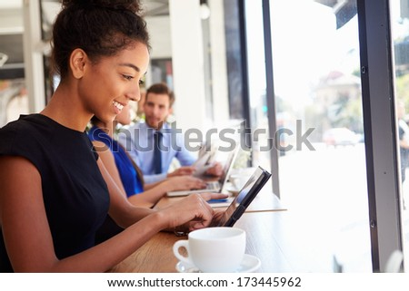 Businesswoman Using Digital Tablet In Coffee Shop - stock photo