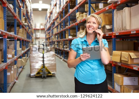Businesswoman Using Digital Tablet In Distribution Warehouse