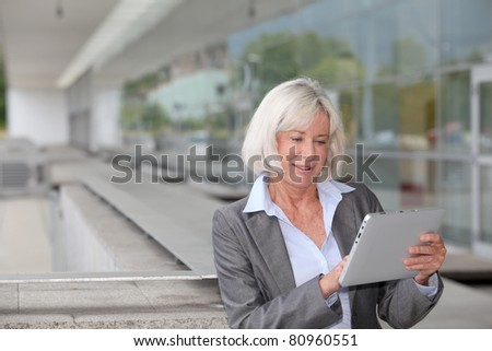 Businesswoman using electronic tablet outside airport - stock photo