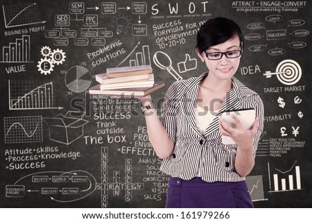 Businesswoman using electronic tablet with books on her hand - stock photo
