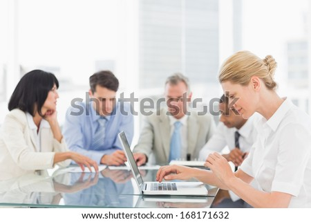 Businesswoman using her laptop during a meeting in the office