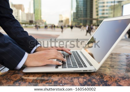 Businesswoman using her laptop in working environment, building background - stock photo