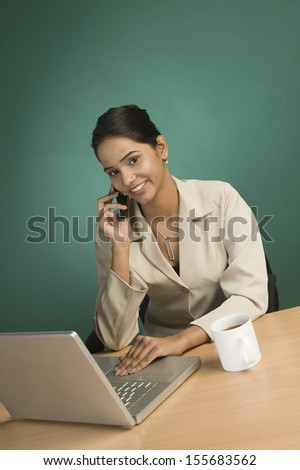 Businesswoman using laptop and talking on mobile phone