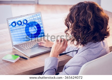Businesswoman using laptop at desk in creative office against blue data