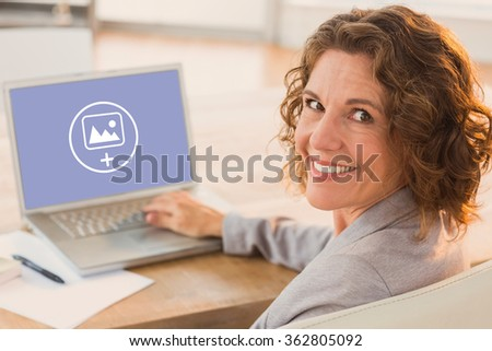 Businesswoman using laptop at desk in creative office against photography apps - stock photo