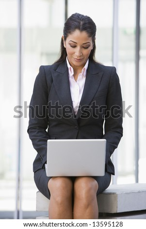 Businesswoman using laptop computer outside office - stock photo