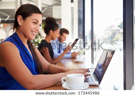 Businesswoman Using Laptop In Coffee Shop - stock photo