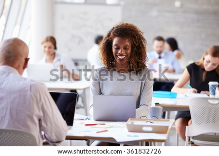 Businesswoman Using Laptop In Customer Service Department