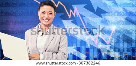 Businesswoman using laptop with colleagues behind against stocks and shares - stock photo