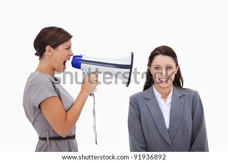 Businesswoman using megaphone to yell at colleague against a white background - stock photo