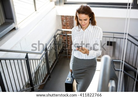 Businesswoman using phone and climbing staircase in office - stock photo