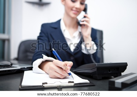 businesswoman using phone, taking notes at office desk - stock photo