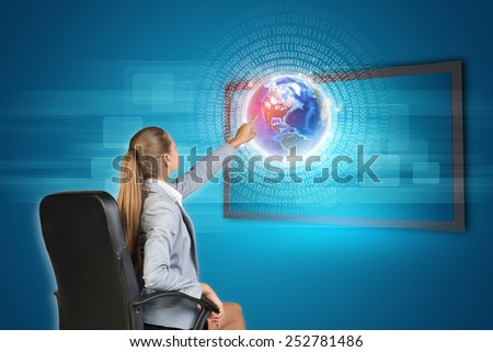 Businesswoman using touch screen interface with Globe and radiant figures, on blue background. Element of this image furnished by NASA - stock photo