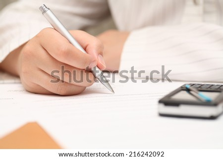 Businesswoman viewing the contract before signing. Closeup. Focus on pen.