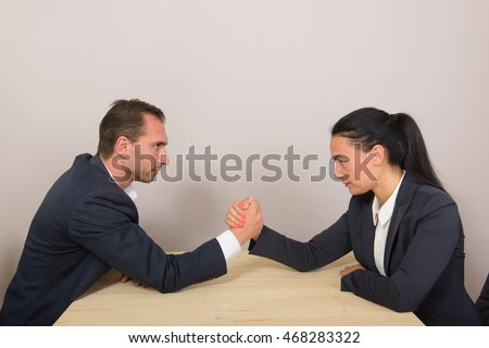 Businesswoman vs businessman - arm wrestling on working table