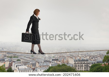 businesswoman walking a tightrope over city rooftops - stock photo