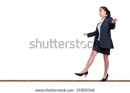 Businesswoman walking along a tightrope, isolated on a white background. - stock photo