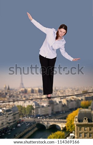 Businesswoman walking along tight rope - stock photo