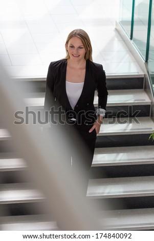 Businesswoman walking down a staircase - stock photo