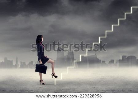 Businesswoman walking up on stairs in cloudy weather