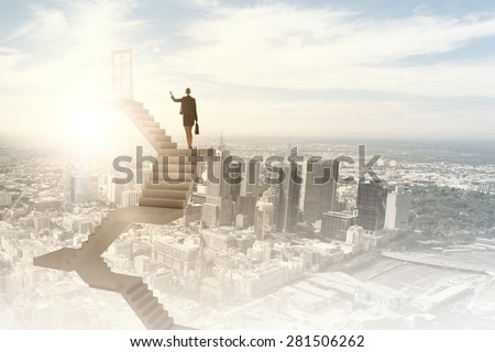 Businesswoman walking up staircase to door in sky - stock photo