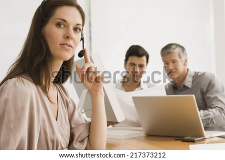 Businesswoman wearing a headset with two businessmen discussing in the background - stock photo