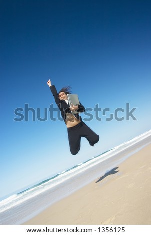 Businesswoman wearing a sunglasses and holding a laptop jumping around - stock photo