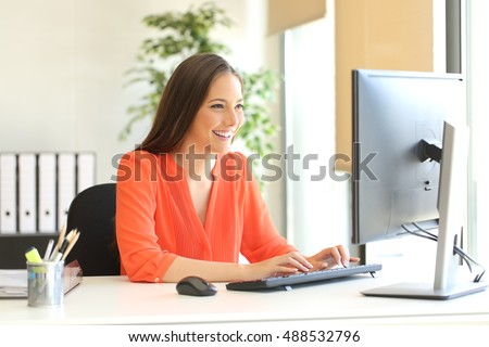 Businesswoman wearing an orange blouse working typing in a desktop computer at office