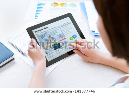 Businesswoman wearing casual shirt sitting at desk and looking latest business news on digital tablet in the office - stock photo