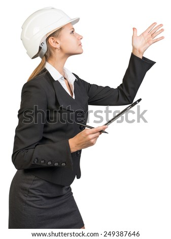 Businesswoman wearing hard hat, with clipboard and pen, pointing at something, peering at it. Isolated over white background - stock photo