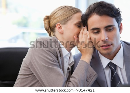 Businesswoman whispering something to her colleague in a meeting room - stock photo