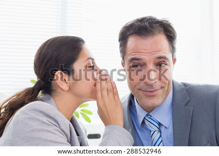 Businesswoman whispering something to her colleague in an office - stock photo