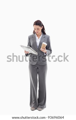 Businesswoman with a coffee reading a newspaper against white background - stock photo