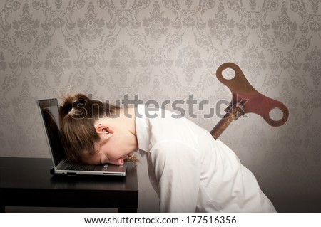 businesswoman with a key winder on her back sleeping on laptop - stock photo