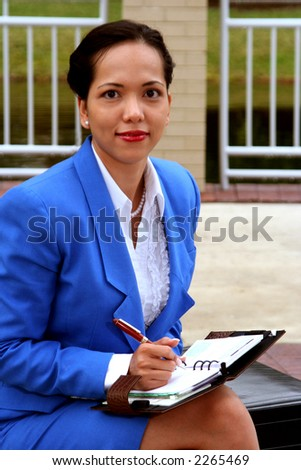 Businesswoman with a planner sitting on a bench