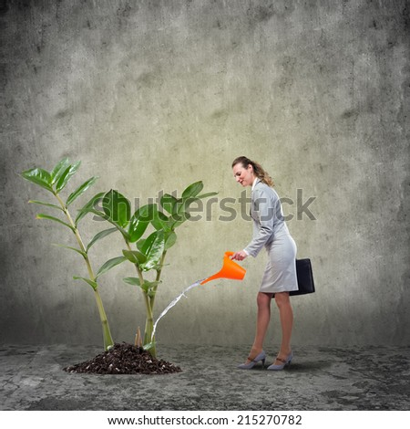 Businesswoman with can watering green money tree