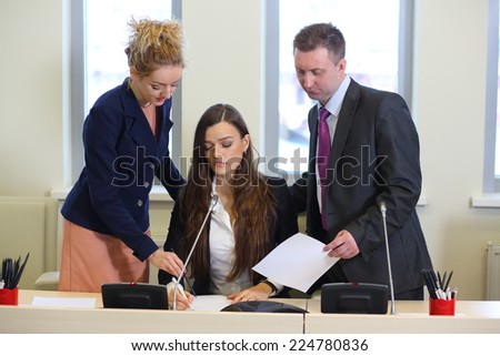 Businesswoman with colleagues corrects documents in the conference hall - stock photo
