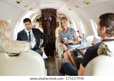 Businesswoman with colleagues having drinks on private jet - stock photo