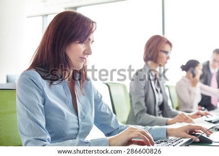 Businesswoman with colleagues working in open plan office - stock photo