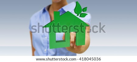 Businesswoman with 3D eco house and energy efficiency in his hand - stock photo